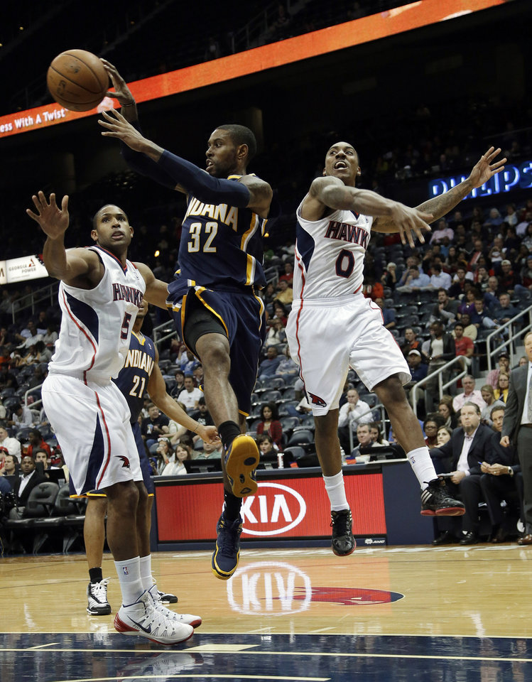 Photo - Indiana Pacers point guard C.J. Watson (32) passed the ball as he drives past Atlanta Hawks' Al Horford, left, and Jeff Teague (0) during the first half of a preseason NBA basketball game Tuesday, Oct. 22, 2013, in Atlanta. (AP Photo/John Bazemore)