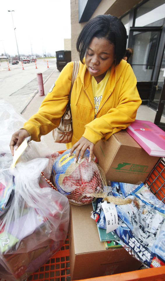 Kari Ivey (CQ ivey), from Oklahoma City, looking at a turkey and gifts loaded into her cart as parents and guardians pick up Angel Tree gifts at the Salvation Army Christmas Center in Midwest City Tuesday, Dec. 20, 2011. Photo by Paul B. Southerland, The Oklahoman ORG XMIT: KOD