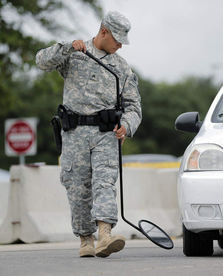 Photo - A mirror is used on a vehicle at a security checkpoint to enter the Lawrence William Judicial Center as the sentencing phase for Maj. Nidal Hasan continues, Tuesday, Aug. 27, 2013, in Fort Hood, Texas. Hasan was convicted of killing 13 of his unarmed comrades in the deadliest attack ever on a U.S. military base. (AP Photo/Eric Gay)