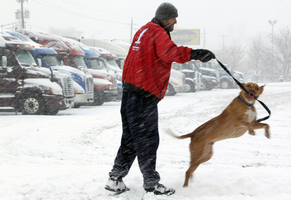 Photo - Trucker Ray Jersey of St. Louis exercises his dog Samson at a truck stop as snow falls in Council Bluffs, Iowa, Thursday, Feb. 21, 2013. Ray Jersey opted to wait the snow storm out as much of the nation's heartland is experiencing heavy snow, treacherous roads and a day off from work or school as a large, potentially dangerous winter storm pushed eastward out of the Rockies. (AP Photo/Nati Harnik)