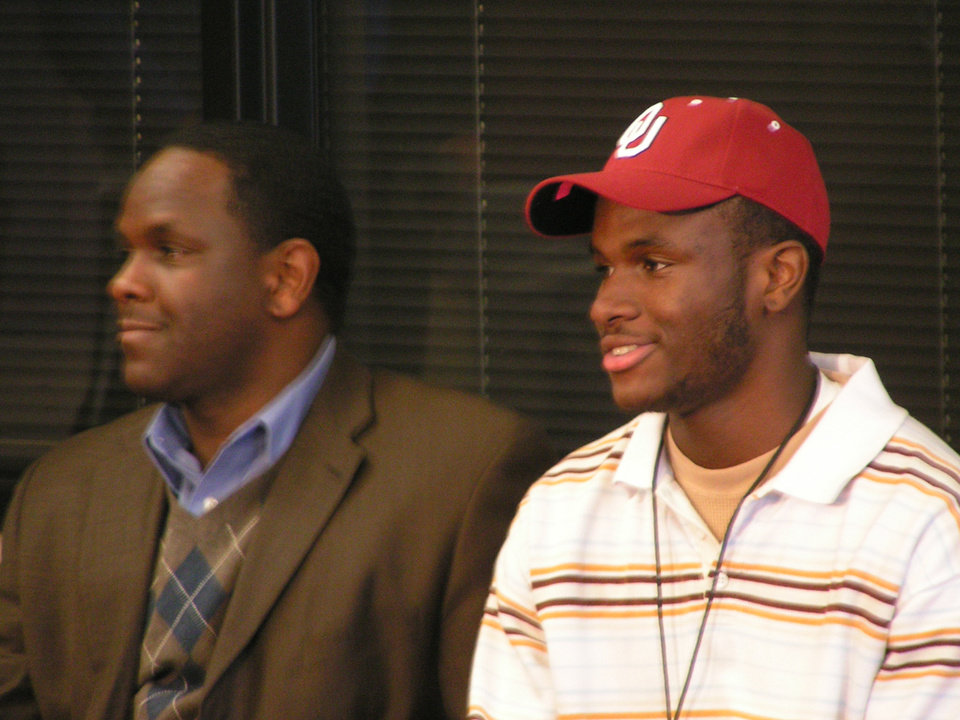 Photo - HIGH SCHOOL FOOTBALL / UNIVERSITY OF OKLAHOMA / COLLEGE FOOTBALL / COMMIT: Jenks star Gabe Lynn, right, announces his commitment to OU as his father, Tyrone Lynn, watches. PHOTO BY RYAN ABER, THE OKLAHOMAN      MINOLTA DIGITAL CAMERA ORG XMIT: 0812182204578671
