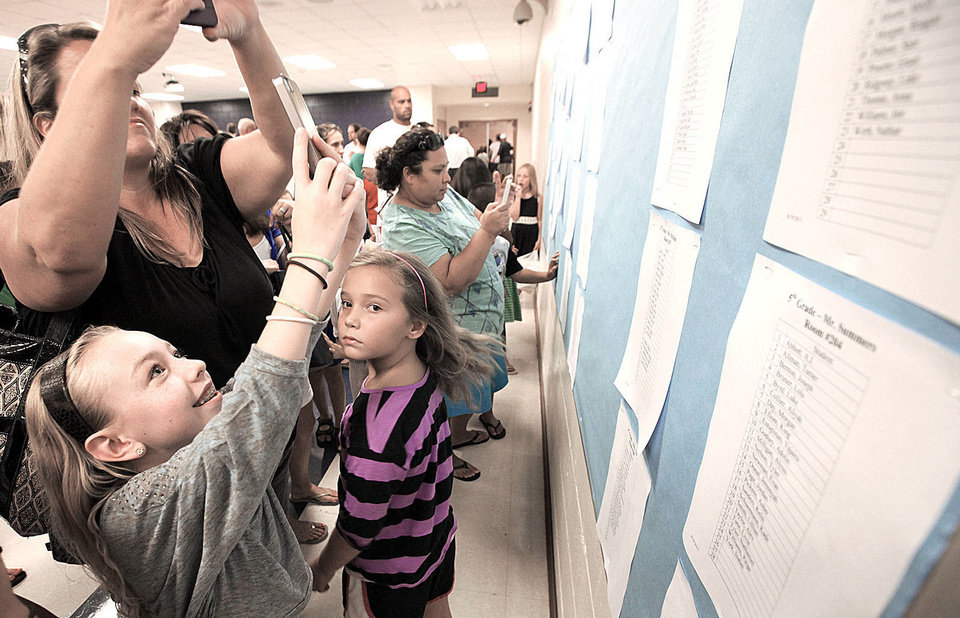Photo - Fourth-grader Madeline McKown takes a photo of her class list during back-to-school night at Cleveland Elementary School in Norman, Monday , August 19, 2013. Photo by David McDaniel, The Oklahoman