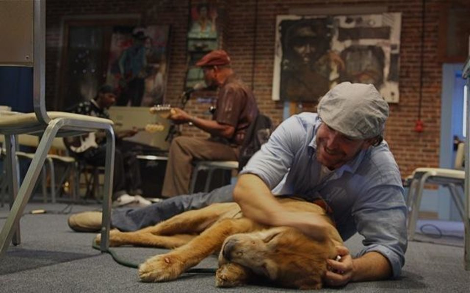 Photo - In this Oct. 2011 photo provided by Explore.org, philanthropist Charlie Annenberg, right, plays with his golden retriever, Lucky, as blues musician James