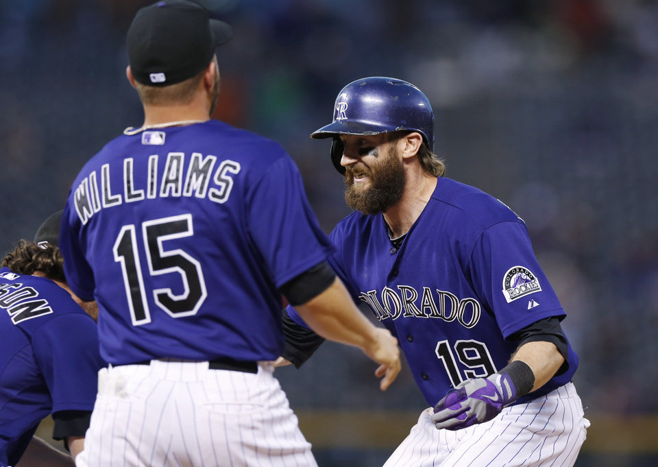Photo - Colorado Rockies' Charlie Blackmon, right, celebrates his walkoff, RBI-single with teammates Charlie Culberson, left, and Jackson Williams against the San Francisco Giants in the ninth inning of the Rockies' 10-9 victory in a baseball game in Denver on Monday, Sept. 1, 2014. (AP Photo/David Zalubowski)