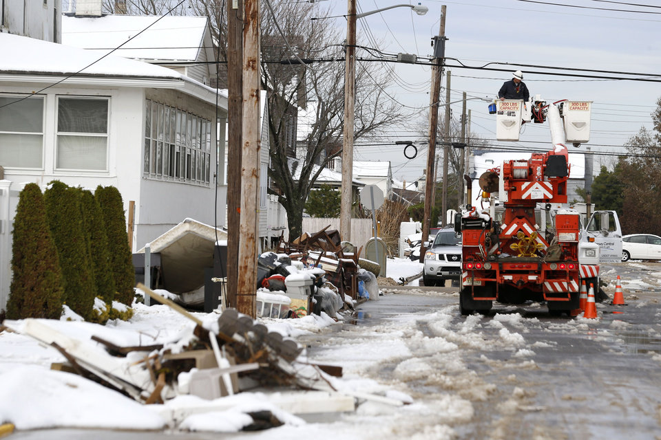 Photo - Utility workers check the power lines as snow covered debris from Superstorm Sandy lay on the side of a street following a nor'easter storm, Thursday, Nov. 8, 2012, in Point Pleasant, N.J.  The New York-New Jersey region woke up to wet snow and more power outages Thursday after the nor'easter pushed back efforts to recover from Superstorm Sandy, that left millions powerless and dozens dead last week. (AP Photo/Julio Cortez) ORG XMIT: NJJC113