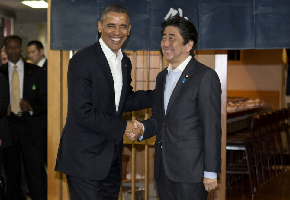 Photo - President Barack Obama and Japanese Prime Minister Shinzo Abe shake hands before having dinner at Sukiyabashi Jiro sushi restaurant in Tokyo, Wednesday, April 23, 2014. Opening a four-country swing through the Asia-Pacific region,  Obama is aiming to promote the U.S. as a committed economic, military and political partner, but the West's dispute with Russia over Ukraine threatens to cast a shadow over the president's sales mission.  (AP Photo/Carolyn Kaster)