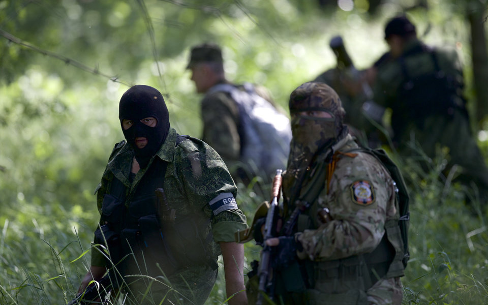 Pro-Russian insurgents  with weapons arrive near the airport outside Donetsk, Ukraine, Monday, May 26, 2014. Ukraine's military launched airstrikes Monday against the separatists who had taken over the airport in the eastern city of Donetsk, suggesting that fighting in the east is far from over. (AP Photo/Vadim Ghirda)