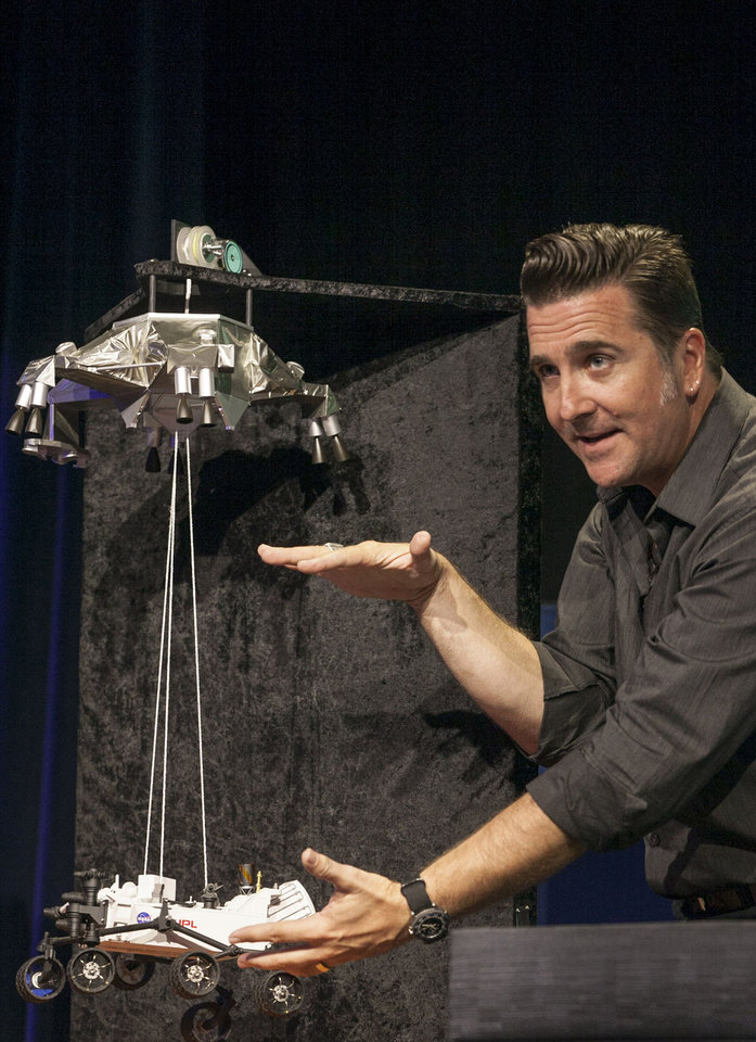 Photo -   FILE - In this file photo taken Thursday, Aug., 2012, Adam Steltzner, Mars Science Laboratory's entry, descent and landing phase leader at JPL uses a scale model to explains the Curiosity rover's Entry, Descent, and Landing (EDL) during the Mission Engineering Overview news briefing at NASA's Jet Propulsion Laboratory in Pasadena, Calif. Curiosity is scheduled to land on Mars Sunday night, Aug. 5, 2012. (AP Photo/Damian Dovarganes, File)