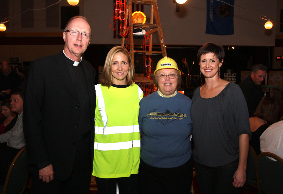 Photo -  Father Rick Stansberry visits with Gwen Poynor, Karen Cartr and Genny Court at Christ the King School's 14th annual auction.
