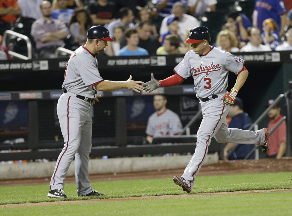 Photo - Washington Nationals' Asdrubal Cabrera (3) celebrates with third base coach Bob Henley (14) on his way to home plate after hitting a home run during the eighth inning of a baseball game Wednesday, Aug. 13, 2014, in New York.  (AP Photo/Frank Franklin II)