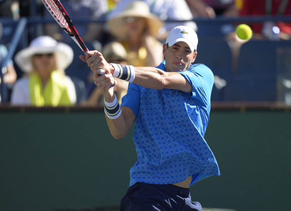 Photo - John Isner volleys with Ernests Gulbis, of Latvia, during their quarterfinal match at the BNP Paribas Open tennis tournament on Friday, March 14, 2014, in Indian Wells, Calif. (AP Photo/Mark J. Terrill)