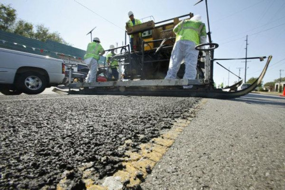 Photo - Crews do micro surfacing on S Pennsylvania Avenue between SW 44 and SW 59 in Oklahoma City on Friday. Micro surfacing extends the life of asphalt roadways and saves money.  PAUL HELLSTERN - The Oklahoman