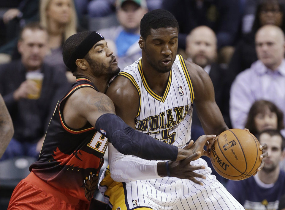 Atlanta Hawks forward Josh Smith, left, tries to knock the ball away from Indiana Pacers center Roy Hibbert in the first half of an NBA basketball game in Indianapolis, Tuesday, Feb. 5, 2013. (AP Photo/Michael Conroy)
