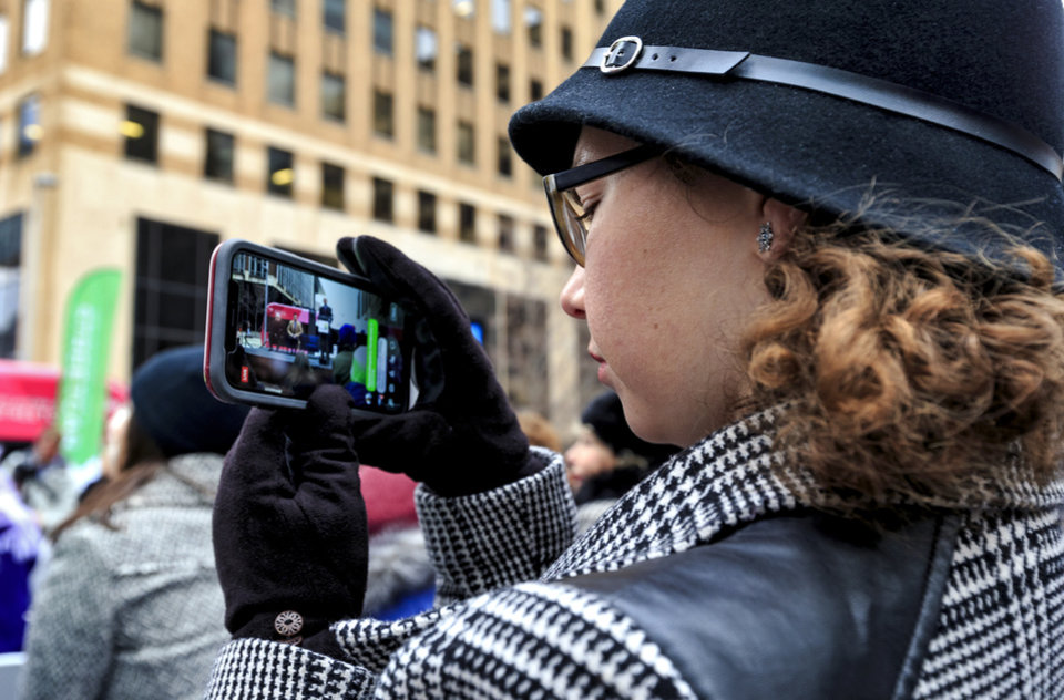 Photo - Katrina Crumbacher shoots video of the grand opening ceremony for the Oklahoma City streetcar system as people gather outside of Leadership Square in downtown Oklahoma City, Okla. on Friday, Dec. 14, 2018. Photo by Chris Landsberger, The Oklahoman