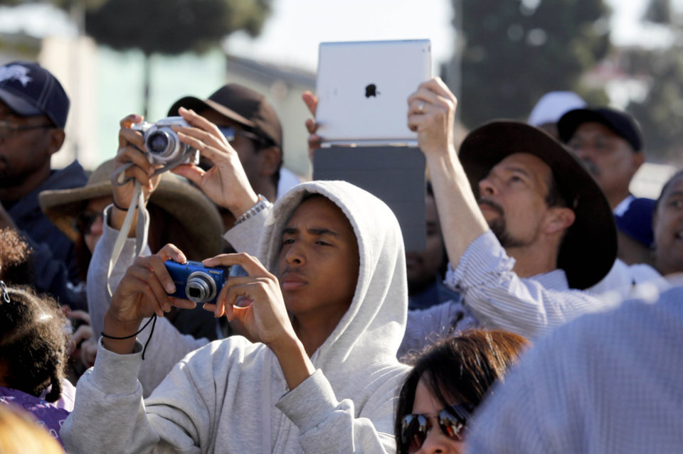Photo -   Spectators photograph the space shuttle Endeavour as it slowly moves down Martin Luther King Blvd. in Los Angeles Sunday, Oct. 14, 2012. In thousands of Earth orbits, the space shuttle Endeavour traveled 123 million miles. But the last few miles of its final journey are proving hard to get through. Endeavour's 12-mile crawl across Los Angeles to the California Science Museum hit repeated delays Saturday, leaving expectant crowds along city streets and at the destination slowly dwindling. Officials estimated the shuttle, originally expected to finish the trip early Saturday evening, would not arrive until later Sunday. (AP Photo/Alex Gallardo)