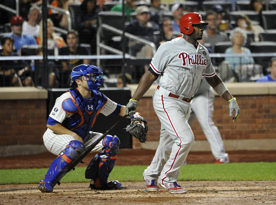 Photo - New York Mets catcher Travis d'Arnaud, left,  and Philadelphia Phillies' Ryan Howard watch Howard's two-run single off of New York Mets starting pitcher Bartolo Colon in the sixth inning of a baseball game at Citi Field on Saturday, Aug. 30, 2014, in New York. (AP Photo/Kathy Kmonicek)