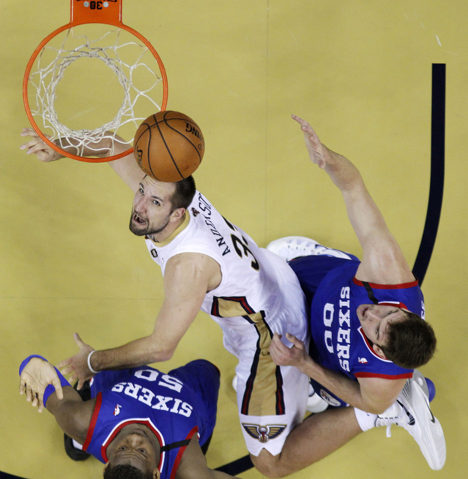 Photo - New Orleans Pelicans power forward Ryan Anderson (33) drives to the basket between Philadelphia 76ers power forward Lavoy Allen (50) and center Spencer Hawes (00) in the first half of an NBA basketball game in New Orleans, Saturday, Nov. 16, 2013. (AP Photo/Gerald Herbert)
