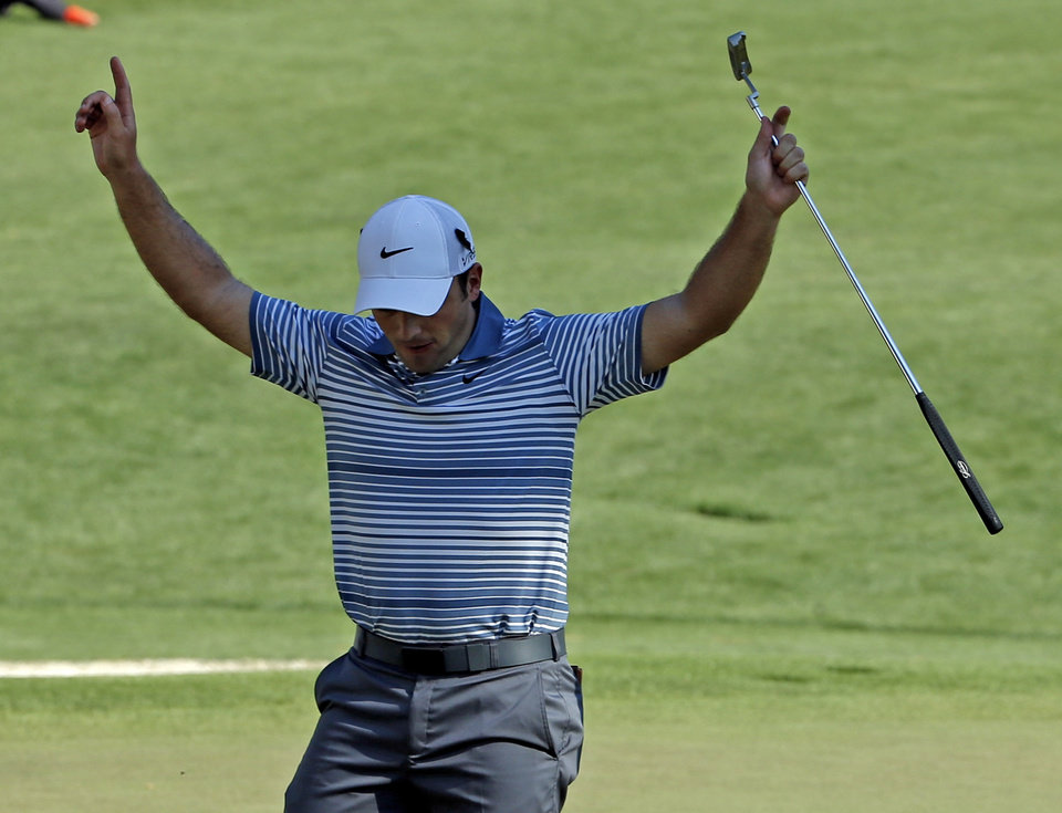 Photo - Francesco Molinari, of Italy, reacts after sinking a putt on the 16th hole during the first round of the Masters golf tournament Thursday, April 10, 2014, in Augusta, Ga. (AP Photo/Matt Slocum)