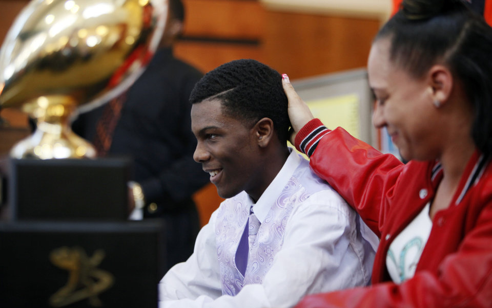 Photo - Amadonna Shaputis, right, touches her son Deonte Childs on the back of his head after Childs signed to play football for Langston during the National Signing Day ceremony at Douglass High School in Oklahoma City, Wednesday, Feb. 1, 2012. Photo by Nate Billings, The Oklahoman