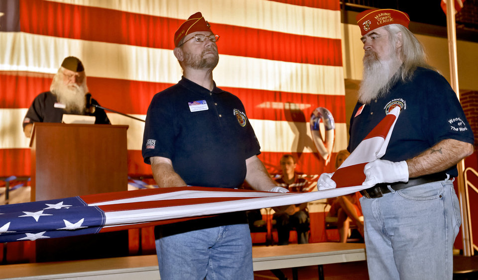 Oklahoma Veterans School Flag Program members Harmon Thompson, left, and Terry Farmer demonstrate the 13 folds of the American flag during Yukon High School's Veterans Day celebration. Photo by Chris Landsberger, The Oklahoman <strong>CHRIS LANDSBERGER - CHRIS LANDSBERGER</strong>