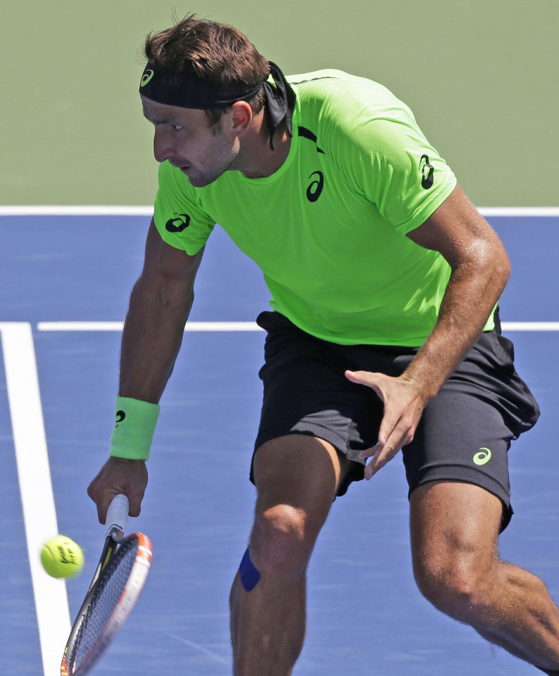 Photo - Marinko Matosevic, from Austrailia, volleys against John Isner during a match at the Western & Southern Open tennis tournament, Wednesday, Aug. 13, 2014, in Mason, Ohio. Isner won 6-3, 7-6 (1). (AP Photo/Al Behrman)