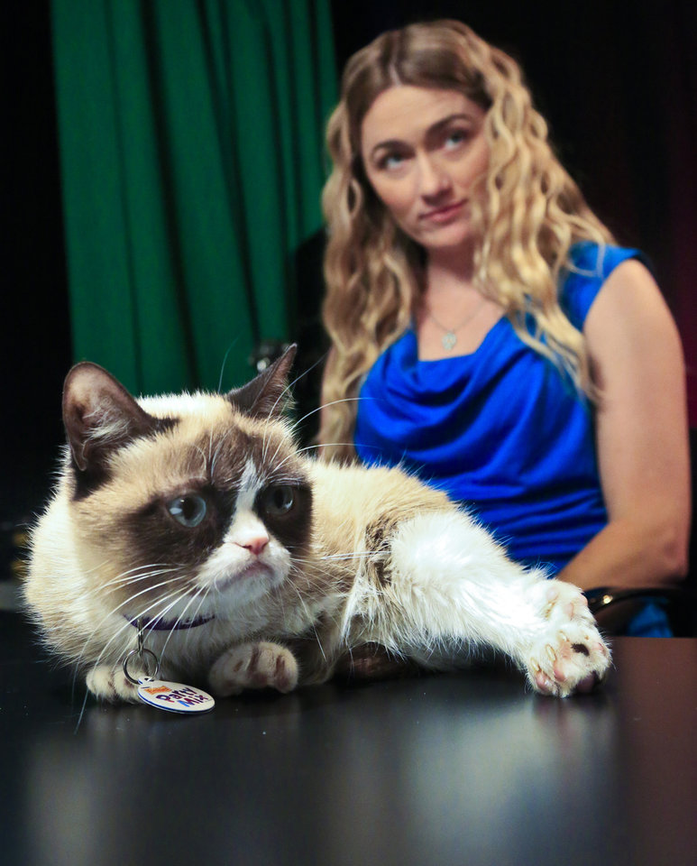 Photo - Tabatha Bundesen and her cat, Grumpy Cat, whose real name is Tardar Sauce, prepare for an interview on Friday April 4, 2014 in New York.  Bundesen says that Grumpy Cat's permanently grumpy-looking face is due to feline dwarfism.  (AP Photo/Bebeto Matthews)