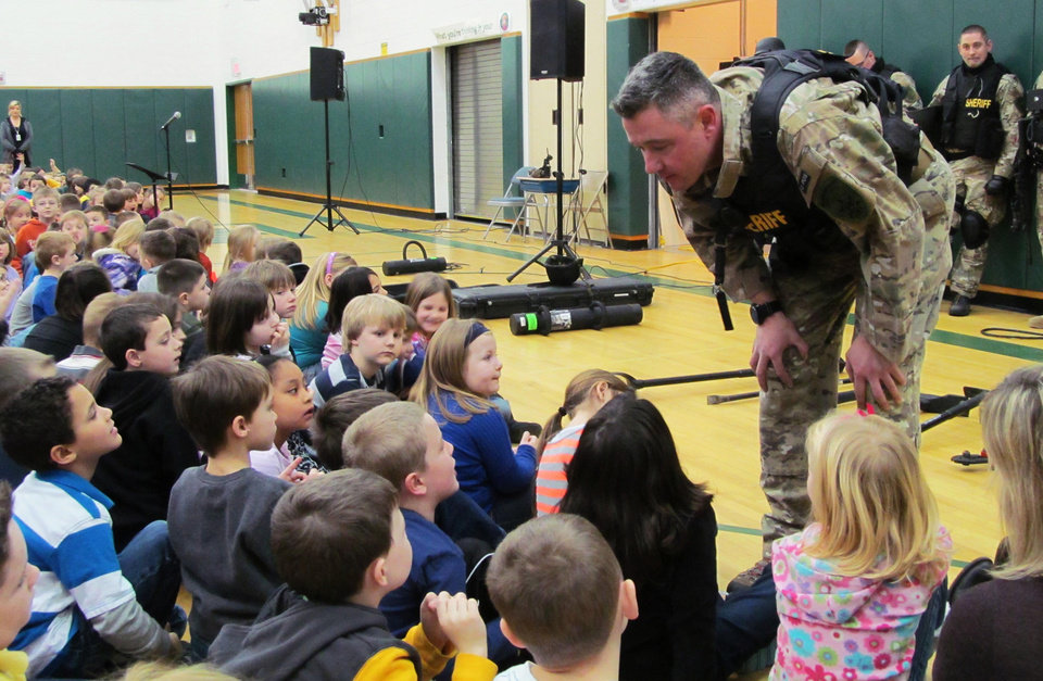 FILE - In this file photo of Jan. 28, 2013, Capt. Bryn Reynolds of the Washington County Sheriff\'s Office takes a question from a student at the Hudson Falls Primary School in Hudson Falls, N.Y. Reynolds and other officers were present to show off their equipment and discuss safety and to practice drills with unloaded guns to prepare for armed intruders at the school. School security has come under more scrutiny in the wake of the Sandy Hook Elementary School massacre in Newtown, Conn., that killed 26 people in December. (AP Photo/The Post-Star, Omar Ricardo Aquije, File)