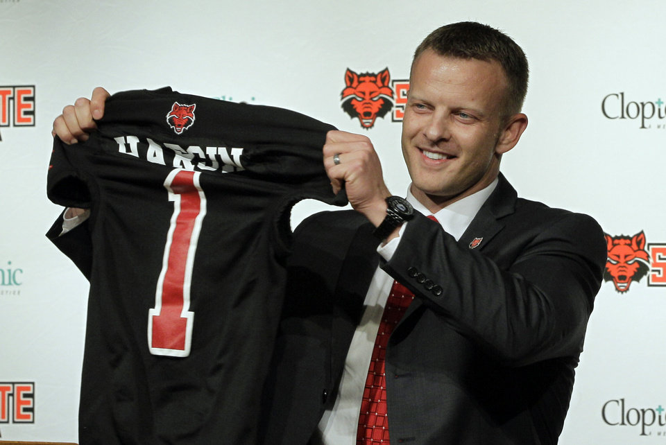 Photo - Former Texas co-offensive coordinator Bryan Harsin holds up an Arkansas State shirt during a news conference introducing him as the new head football coach of the school, Wednesday, Dec. 12, 2012, in Jonesboro, Ark. (AP Photo/Danny Johnston)