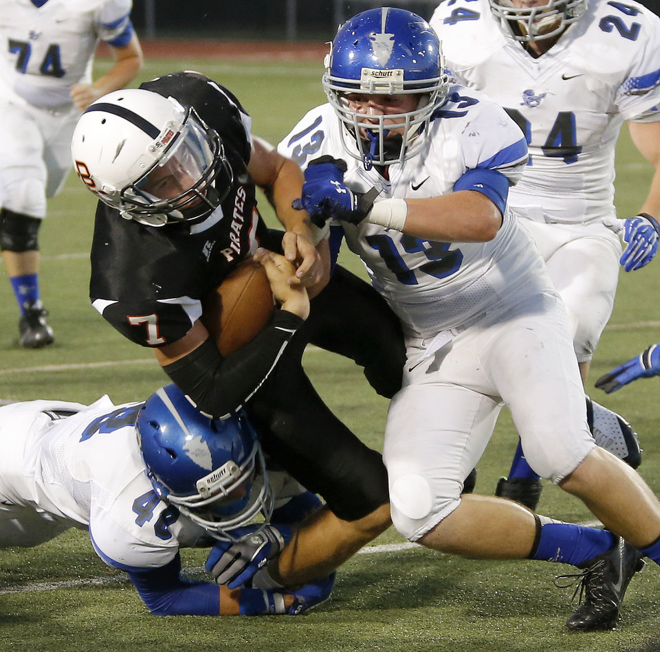 Putnam City's Braden Hudson is brought down by Sapulpa's Tanner Gregory (42) and Jacob Shanahan (13) during their high school football game at Putnam City in Oklahoma City, Thursday, Sept. 26, 2013. Photo by Bryan Terry, The Oklahoman