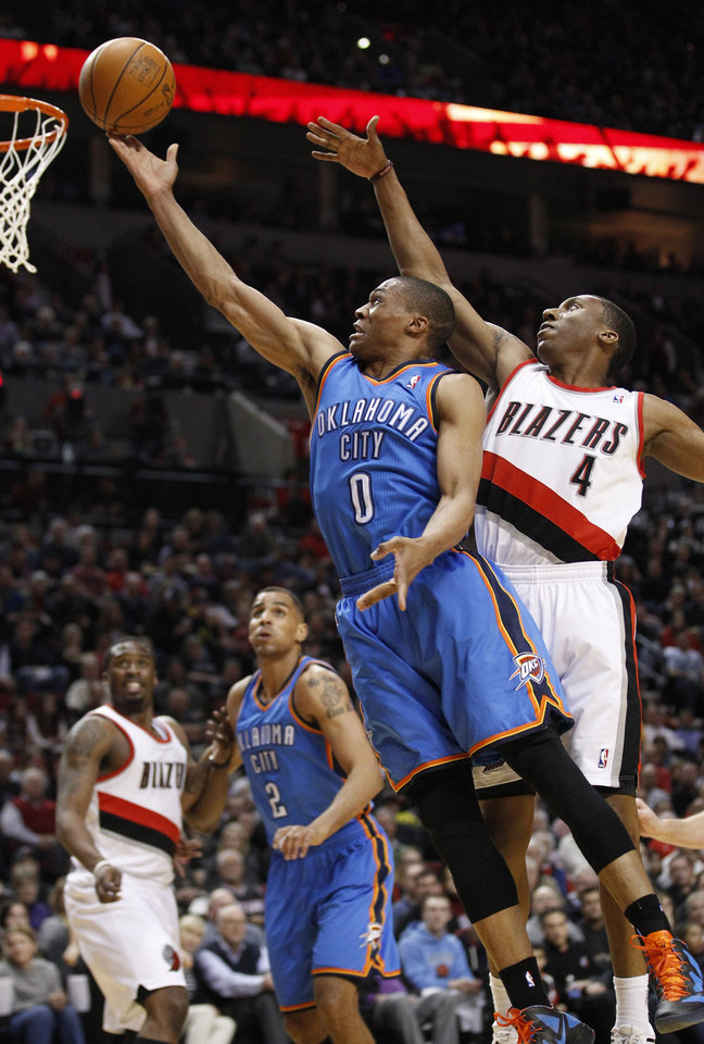 Oklahoma City Thunder\'s Russell Westbrook (0) lays the ball up as Portland Trail Blazers\' Nolan Smith (4) defends in the first quarter during an NBA basketball game, Tuesday, March 27, 2012, in Portland, Ore. (AP Photo/Rick Bowmer)