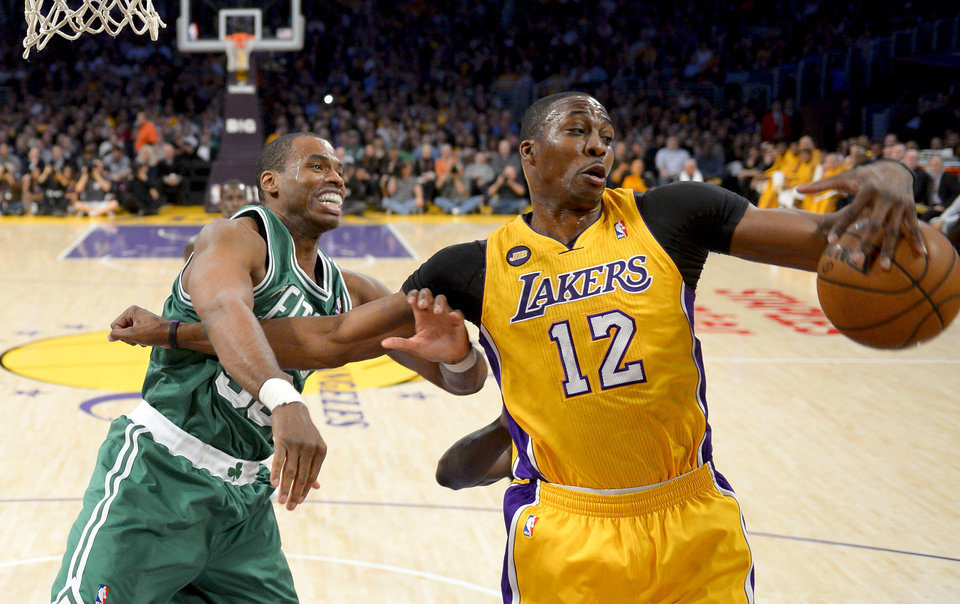 Photo - FILE - Boston Celtics center Jason Collins battles Los Angeles Lakers center Dwight Howard (12) for a rebound during the first half of their NBA basketball game, Wednesday, Feb. 20, 2013 in Los Angeles. NBA veteran center Collins has become the first male professional athlete in the major four American sports leagues to come out as gay. Collins wrote a first-person account posted Monday, April 29, 2013 on Sports Illustrated's website.(AP Photo/Mark J. Terrill, File)