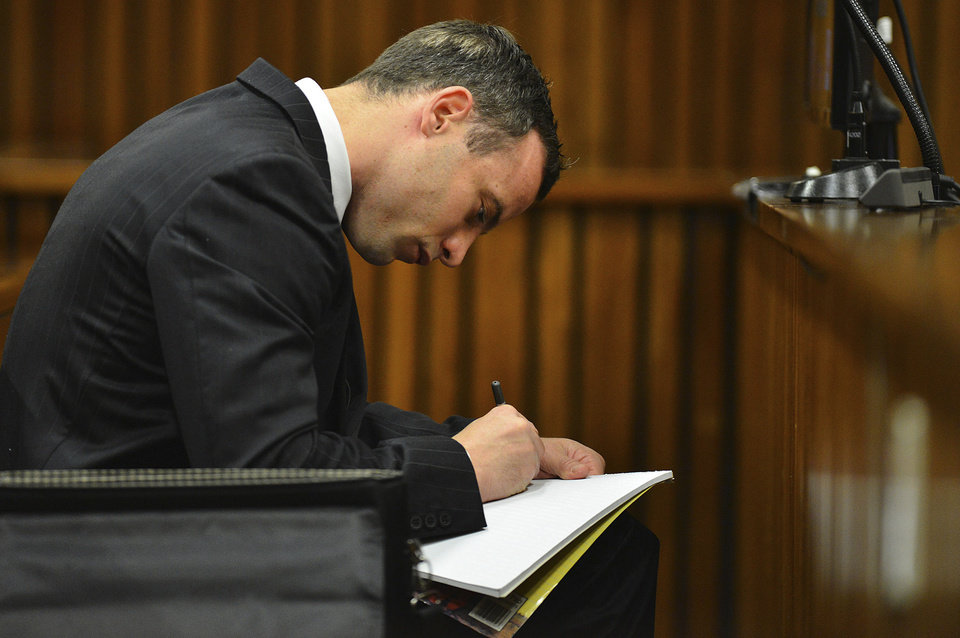 Photo - Oscar Pistorius makes a note in court in Pretoria, South Africa, June 30, 2014. The murder trial of Pistorius resumed Monday after one month during which mental health experts evaluated the athlete to determine if he has an anxiety disorder that could have influenced his actions on the night he killed his girlfriend Reeva Steenkamp. (AP Photo/Phill Magakoe, Pool)
