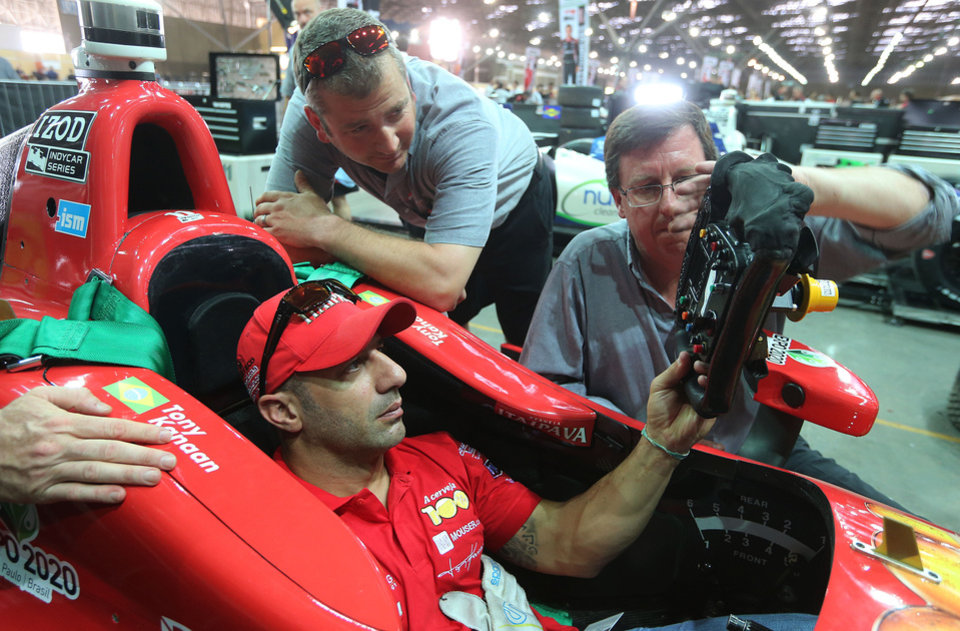 IndyCar driver Tony Kanaan, of Brazil, sits in his car and holds a steering wheel as he talks with members of his team in the garage area at the track in Sao Paulo, Brazil, Friday, May 3, 2013. Brazil will host the 4th race of the Indy Car season on May 5. (AP Photo/Andre Penner)