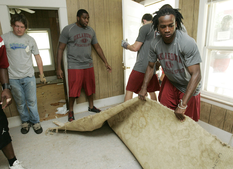 Photo - UNIVERSITY OF OKLAHOMA, CLEAN UP: Far right -Ryan Broyles and other OU football teammates and volunteers remove carpet during a Habitat for Humanity cleanup Friday, July 20, 2007 in Noble, OK. BY JACONNA AGUIRRE/THE OKLAHOMAN. ORG XMIT: KOD