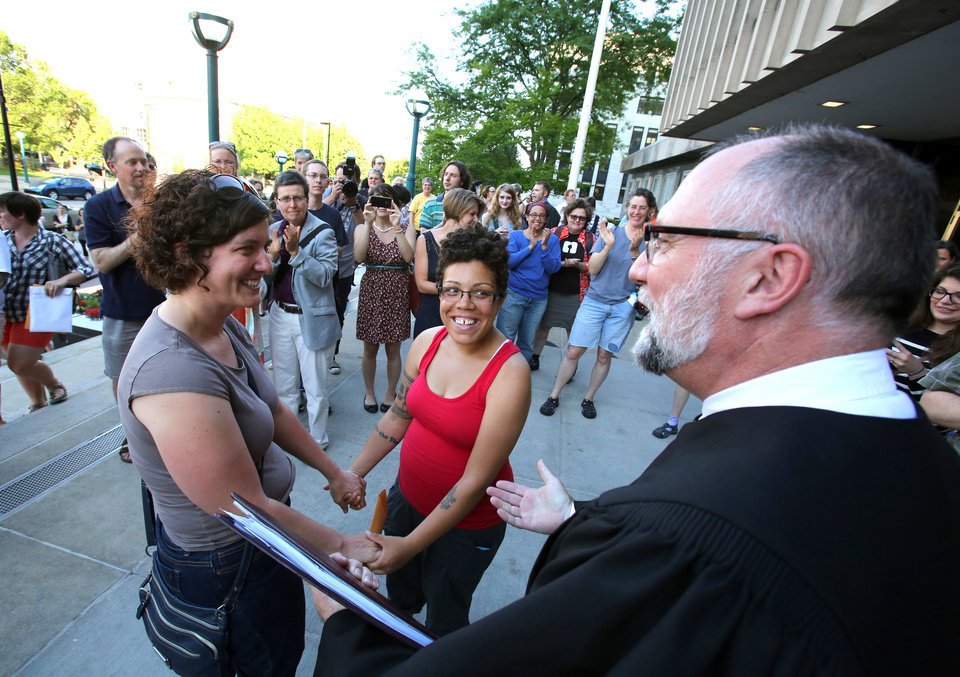 Photo - Mel Freitag, left, and Amber Sowards, of Madison, Wis., get married by Daniel Floeter, family court commissioner, outside the City-County Building on Friday, June 6, 2014, in Madison after a federal judge struck down the state's ban on same-sex marriage. Sowards, who is six months pregnant, has been with Freitag for six years. (AP Photo/Wisconsin State Journal, Amber Arnold)