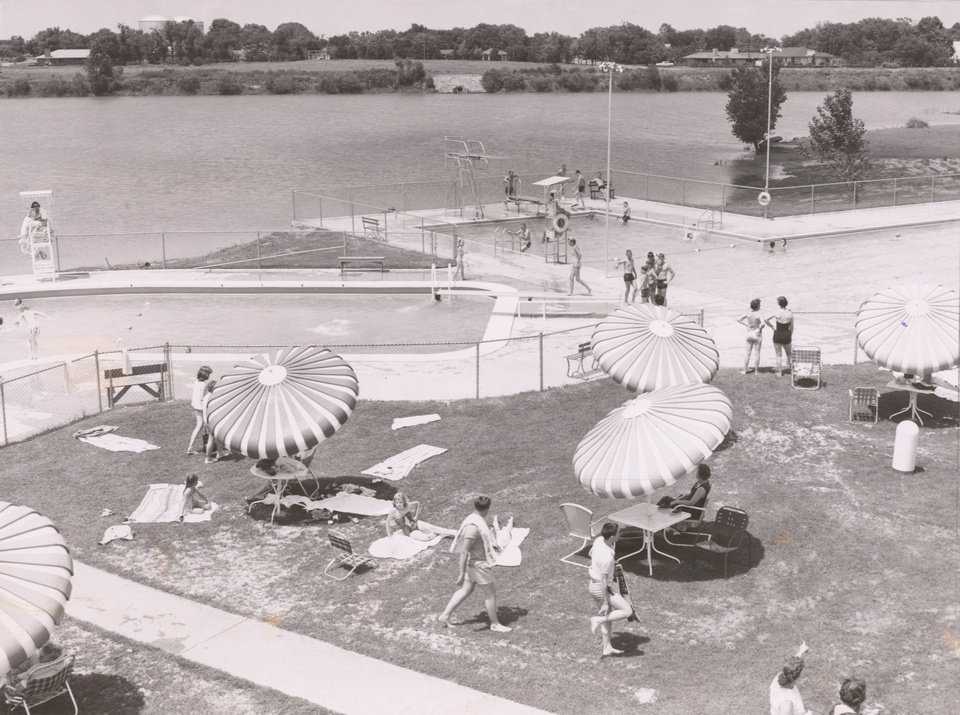 Beach umbrellas dot the grassy lawn at Sportsman's Country club as  swimmers cool off in the club's twin pools, in this June 1957 photo. <strong> - The Oklahoman archives</strong>