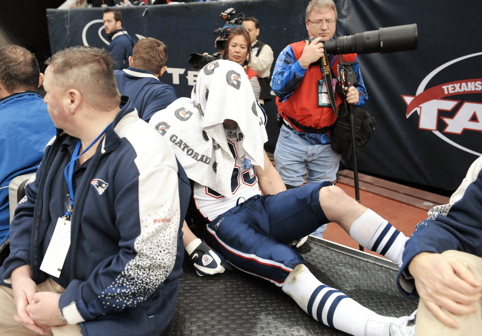 Photo - New England receiver Wes Welker is driven off the field after suffering a season-ending knee injury on Jan. 3 in Houston. AP photos
