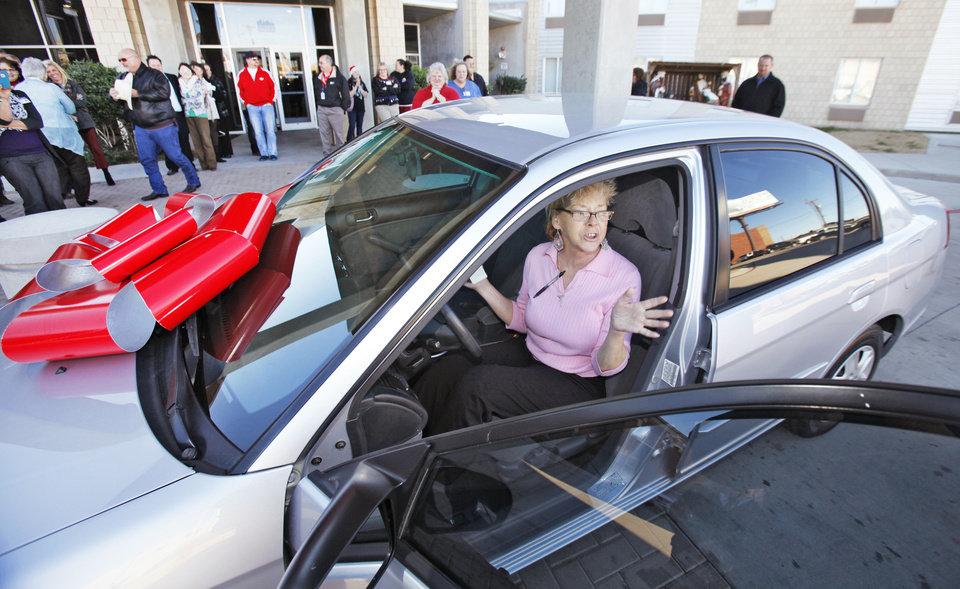 Photo - City Rescue Mission resident Peggy Vanisko reacts to being given a car for Christmas. The car was donated by AAA Oklahoma and repaired by Body Works Collision Centers. Photo by David McDaniel, The Oklahoman
