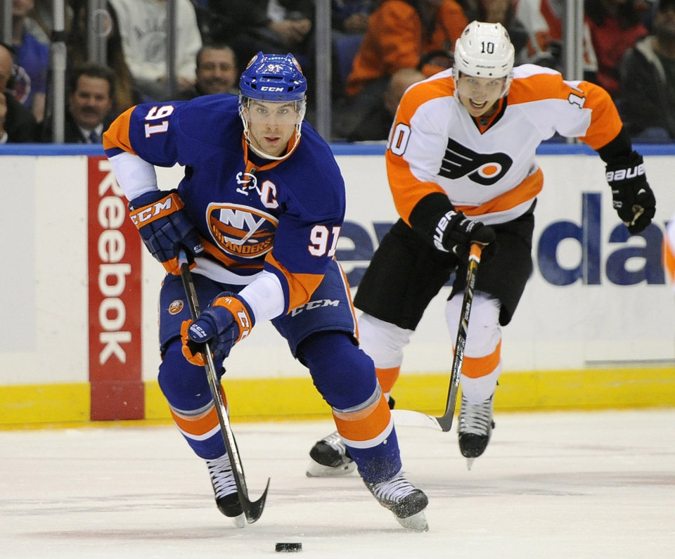 Photo - New York Islanders' John Tavares (91) drives the puck down ice away from Philadelphia Flyers' Brayden Schenn (10) in the second period of an NHL hockey game at the Nassau Coliseum on Saturday, Oct. 26, 2013, in Uniondale, N.Y. (AP Photo/Kathy Kmonicek)