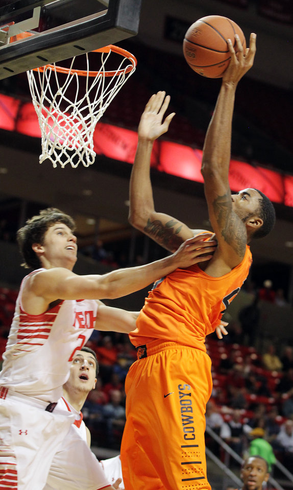 Photo - Oklahoma State's Michael Cobbins, right, shoots against Texas Tech's Dusty Hannahs during their NCAA college basketball game, Wednesday, Feb. 13, 2013, in Lubbock, Texas. (AP Photo/The Avalanche-Journal, Zach Long) ALL LOCAL TV OUT