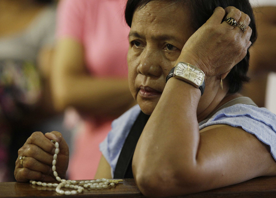 A Filipino devotee prays at the Shrine of Our Lady of Perpetual Help in suburban Paranaque, south of Manila, Philippines on Sunday March 3, 2013. Filipinos in Asia's largest predominantly Roman Catholic nation on Sunday went to church that awkwardly had no pope for the first time in 600 years because of Benedict XVI's resignation. They prayed for the smooth rise of a successor who can lead the church. (AP Photo/Aaron Favila)