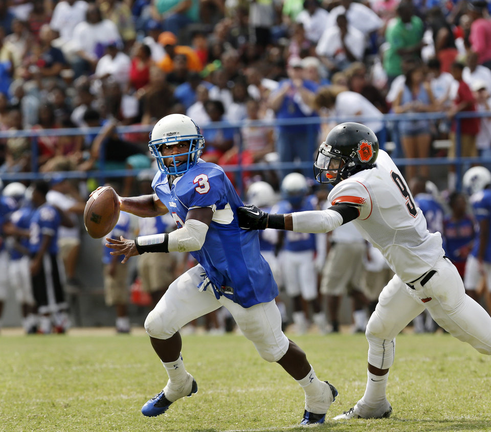 Photo - Millwood quarterback Cameron Batson is chased by Douglass' Isiah Shaputis  during the annual Soul Bowl football game  between the  Douglass Trojans and  the Millwood Falcons at Leodies Robinson Field in Oklahoma City on  Saturday, Sep. 14, 2013. Millwood defeated Douglass, 31-12.    Photo  by Jim Beckel, The Oklahoman.