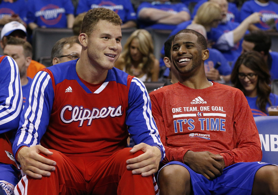 Photo - Los Angeles Clippers guard Chris Paul, right, laughs with teammate Blake Griffin, left, as they sit on the bench in the fourth quarter of Game 1 of the Western Conference semifinal NBA basketball playoff series in Oklahoma City, Monday, May 5, 2014. Los Angeles won 122-105. (AP Photo/Sue Ogrocki)