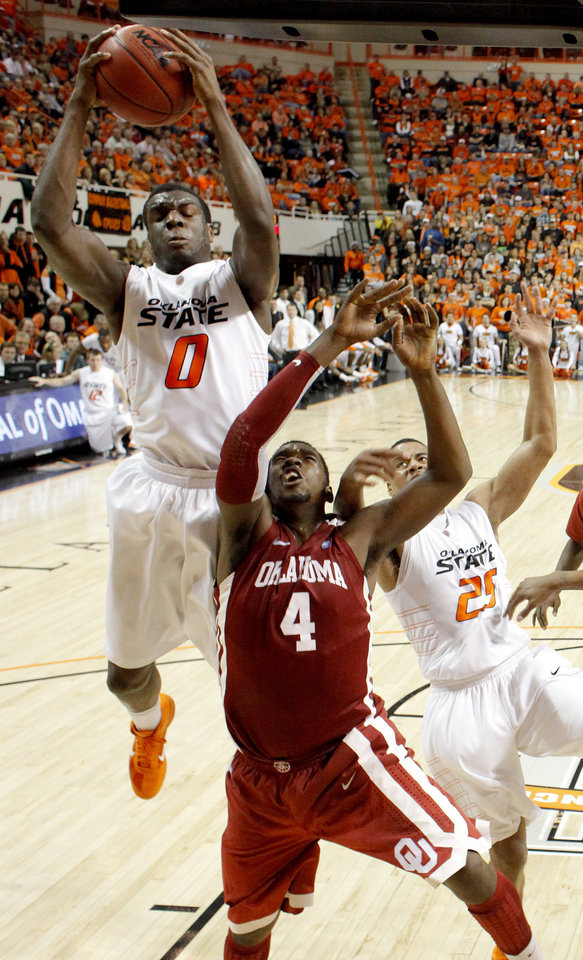 Photo - Oklahoma State's Jean-Paul Olukemi (0)grabs the ball over Oklahoma's Andrew Fitzgerald (4) and Oklahoma State's Darrell Williams (25) during the Bedlam men's college basketball game between the University of Oklahoma Sooners and Oklahoma State University Cowboys at Gallagher-Iba Arena in Stillwater, Okla., Saturday, February, 5, 2011. Photo by Bryan Terry, The Oklahoman