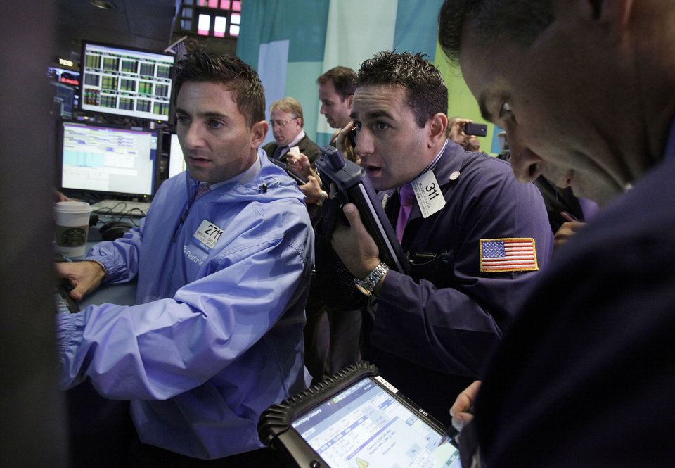 Photo -   Trader Michael Liloia, center, works on the floor of the New York Stock Exchange Friday, Oct. 5, 2012. Stocks are rising in early trading on Wall Street after the government reported that the U.S. unemployment rate fell below 8 percent for the first time in almost four years. (AP Photo/Richard Drew)