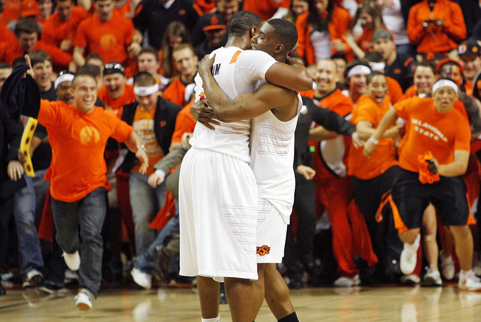 Photo - OSU's Matt Pilgrim (31), left, and Obi Muonelo (2) hug as fans take the court at the end of the men's college basketball game between the University of Kansas (KU) and Oklahoma State University (OSU) at Gallagher-Iba Arena in Stillwater, Okla., Saturday, Feb. 27, 2010. OSU won, 85-77. Photo by Nate Billings, The Oklahoman