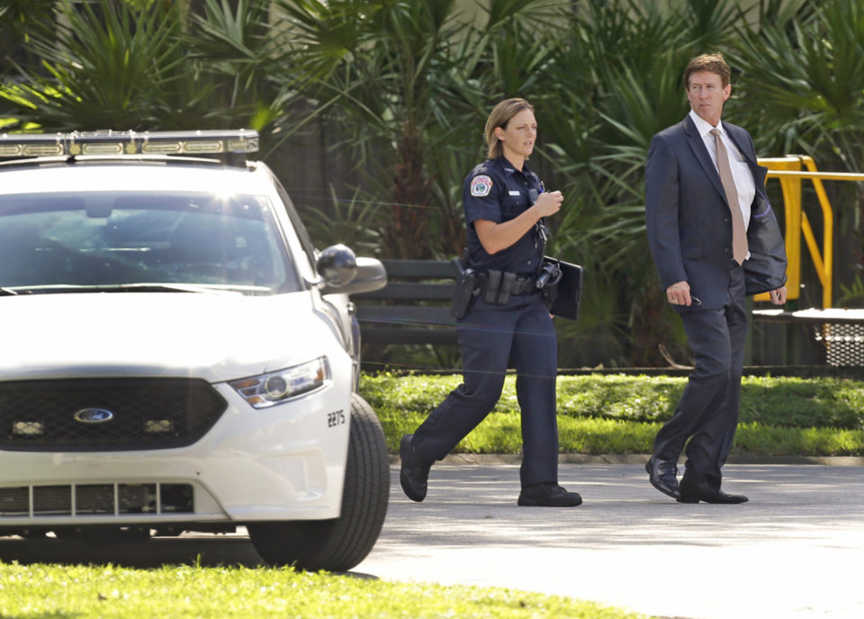 Photo - Mark O'Mara, attorney for George Zimmerman, speaks with a police officer at the scene of a domestic incident in the Lake Mary, Fla. neighborhood where Zimmerman and his wife Shellie had lived during his murder trial, Monday, Sept. 9, 2013. Zimmerman's wife says on a 911 call that her estranged husband punched her father in the nose, grabbed an iPad out of her hand and smashed it and threatened them both with a gun. Zimmerman was recently found not guilty for the 2012 shooting death of Trayvon Martin. (AP Photo/John Raoux)
