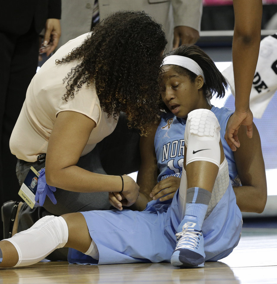 Photo - North Carolina's Danielle Butts, right, is examined by a trainer after being injured during the first half of an NCAA college basketball semi-final game against Duke at the Atlantic Coast Conference tournament in Greensboro, N.C., Saturday, March 8, 2014. (AP Photo/Chuck Burton)