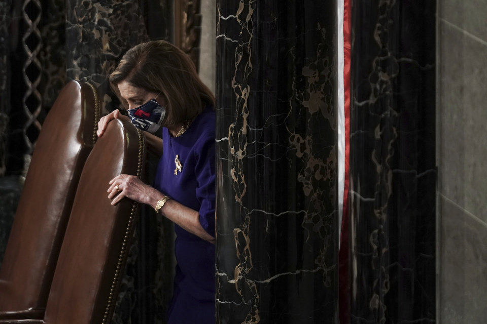 Photo - Speaker of the House Nancy Pelosi, D-Calif., calls the House in order prior to a joint session of the House and Senate convenes to confirm the Electoral College votes cast in November's election, at the Capitol in Washington, Wednesday, Jan. 6, 2021. (Greg Nash/Pool via AP)
