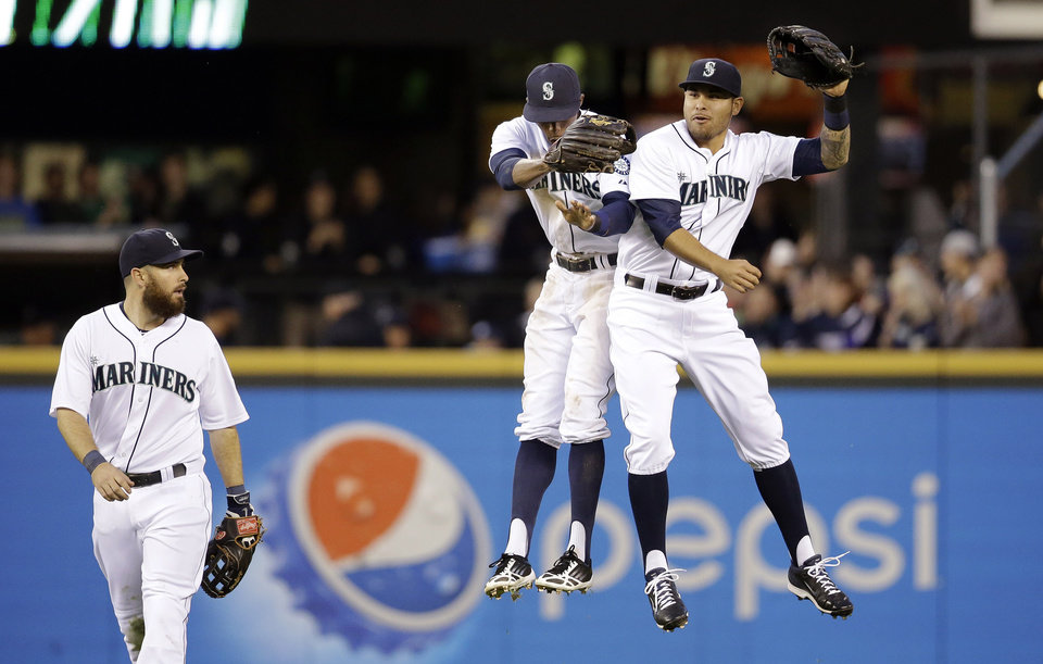 Photo - Seattle Mariners left fielder Dustin Ackley, left, looks on as center fielder James Jones, center, and right fielder Stefen Romero leap together after the team beat the Kansas City Royals in a baseball game Saturday, May 10, 2014, in Seattle. The Mariners won 3-1. (AP Photo/Elaine Thompson)